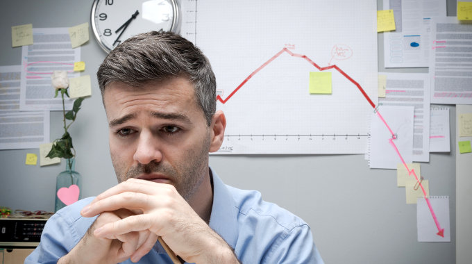 Pensive businessman at work with negative financial chart on background.